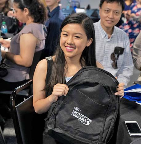 Female student holding Ford Driving Dreams backpack