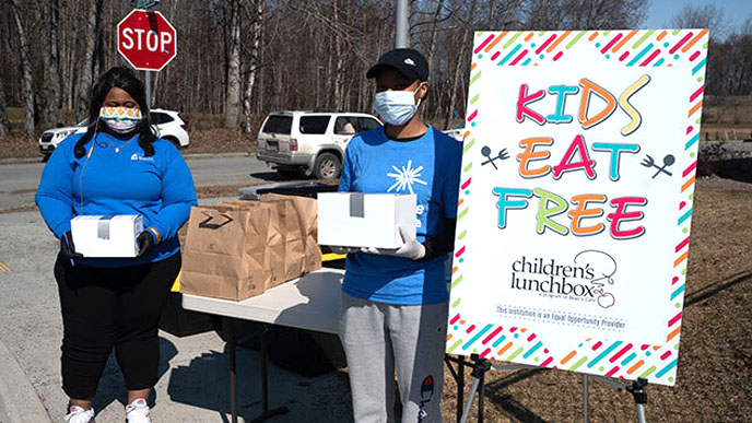 A female and male persons of color, masked, gloved holding boxes stand in front of a table of kraft paper bags and beside a sign with KIDS EAT FREE and  Children's Lunchbox logo