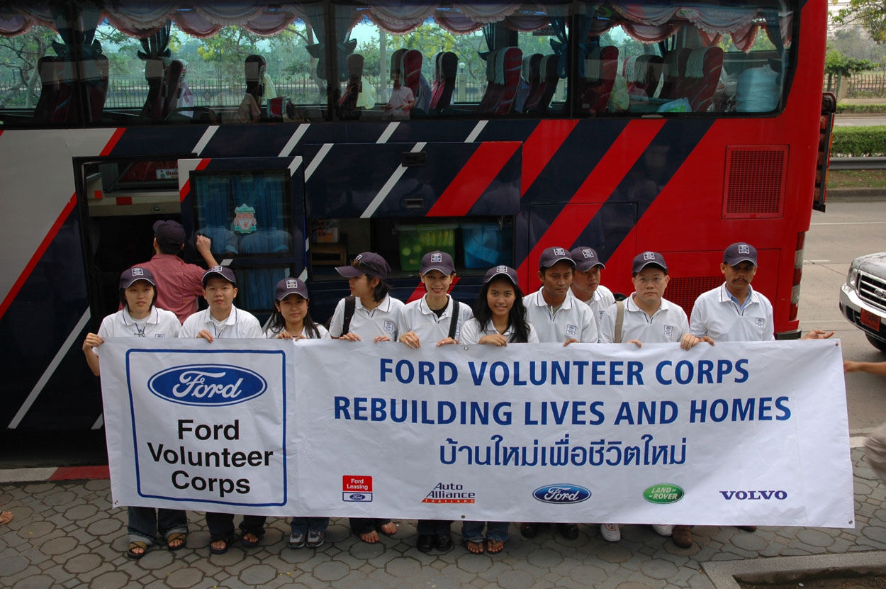 10 people wearing Ford Volunteer Corps baseball style hats, holding banner that includes FORD VOLUNTEER CORPS REBUILDING LIVES AND HOMES