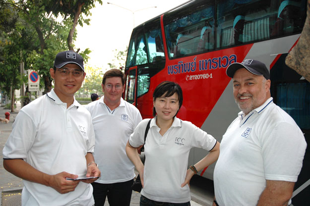 Asian male and female and two white males beside a travel bus.