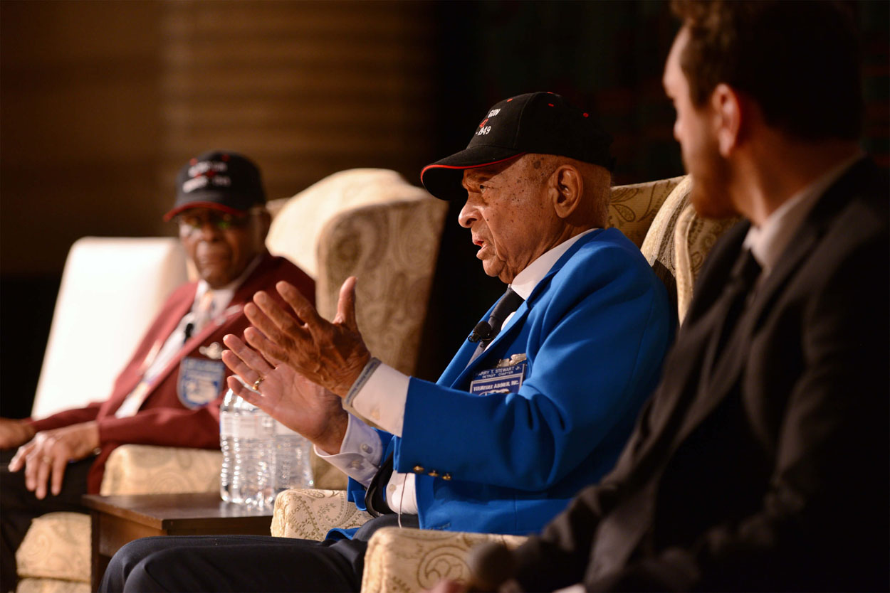 Lt. Col. Stewart talking to the Curious Minds audience while seated on stage between another Tuskegee Airman and unidentified white male