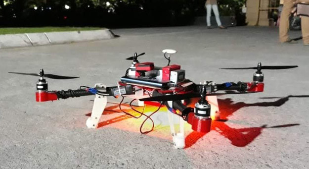 Red and white drone with feet of audience visible in background