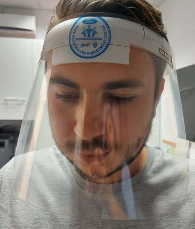 Male wearing face shield with Ford Resource and Engagement Center logo on headband