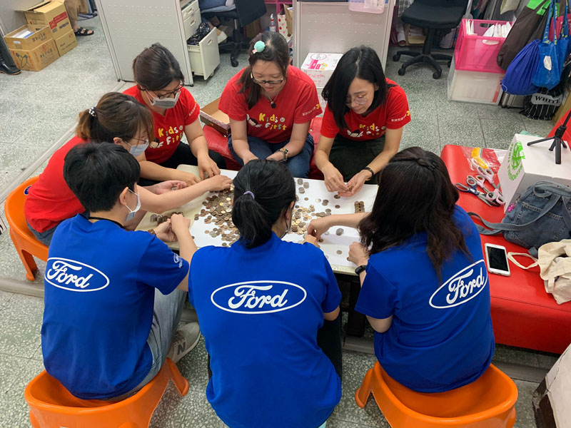 7 people sitting around table, 3 with blue Ford T-shirts sorting coins in China