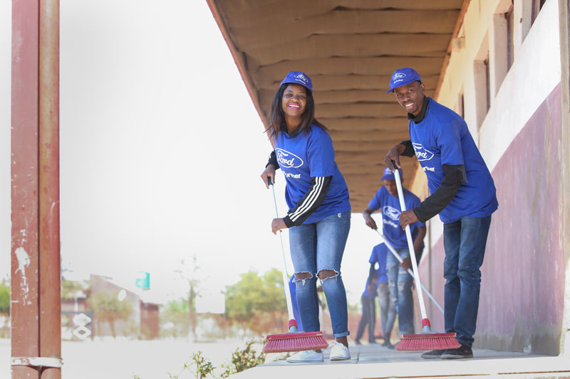 Female and male in blue Ford attire pushing brooms on covered walkway, more volunteers in background