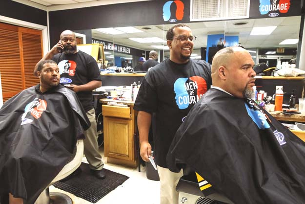 Tommy Mays standing behind male in barber chair with another customer in a chair with a barber to Mays' right