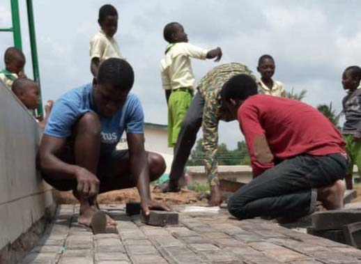 Laying plastic paver bricks made with grant funds