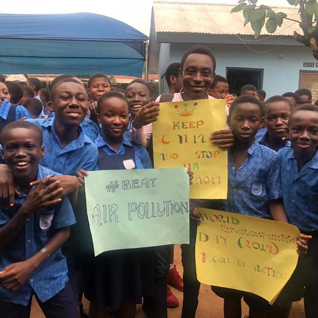 Kwame Nkrumah University of Science and Technology, Kumasi students in blue uniforms with adult, holding anit-air pollution signs