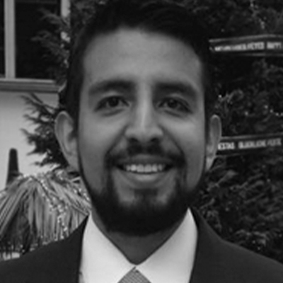 Jose Adan Cortina head shot in black and white, light shirt with dark suit jacket and tie and short dark hair with mustache and connected goatee