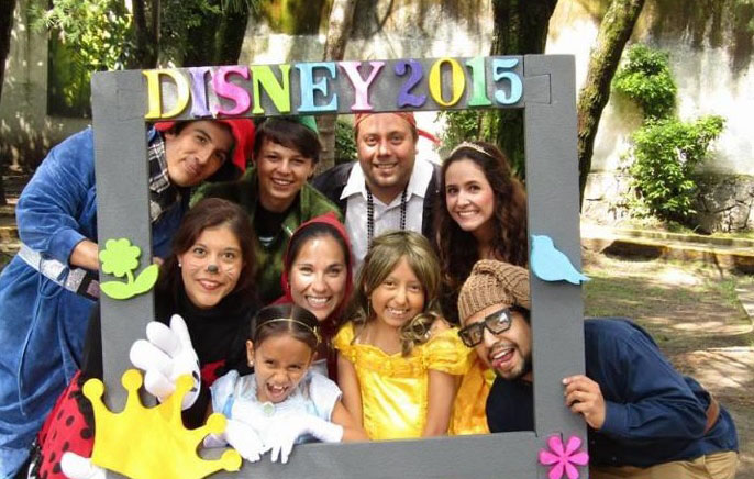 7 adults, two children inside a photo frame with DISNEY 2015, all dressed in assortment of Disney character costumes.