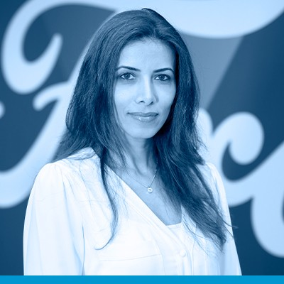 Rania Al-Shurafa, head shot in black and white with blue overlay, wearing light V-neck top and jacket, long dark hair in front of Ford background