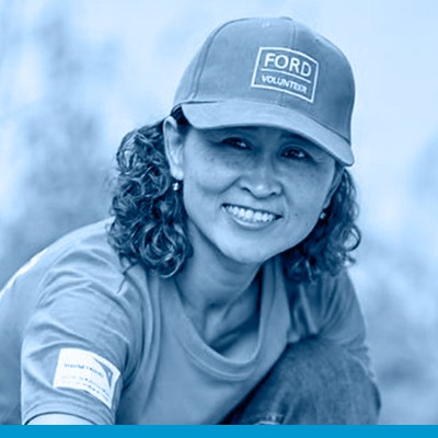 Candy Sukkamon Sopachote head shot in black and white with blue overlay, wearing medium colour trucker-style hat with FORD VOLUNTEER on the front, with similar colour T-shirt and jeans, dark curly hair as she partially sits on the ground