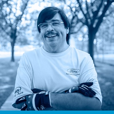 Roberto Teran head shot in black and white with blue overlay, dark hair, wire framed glasses, mustache, Ford Community Corps T-shirt and work gloves