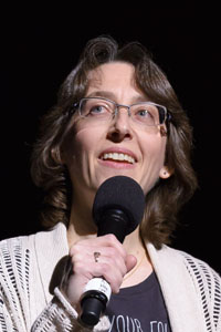 White female, shoulder-length, wavy brown hair, frame-less eye glasses, white knit jacket over dark T-shirt standing with microphone in her right hand