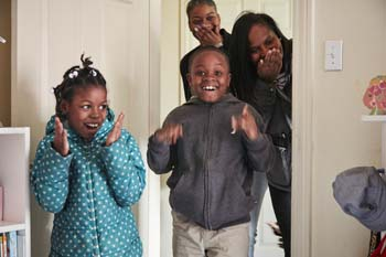 Three children and female adult expressing surprise seeing a newly furnished room