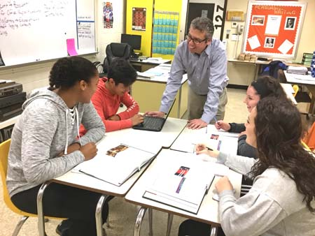 Dan Greenberg talks with two male and two female students at a table in a classroom