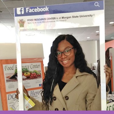 Collegiate age, female, African American student holding facebook frame displaying FOOD RESOURCE CENTER is at Morgan State University while standing in front of FRC display