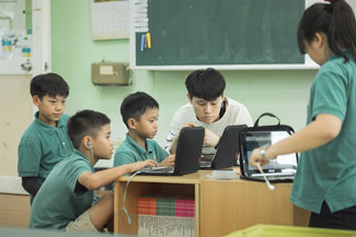 Five children, four in green polo style shirts. Three juveniles viewing two laptops with an young person in a white sweater. Fourth student stands facing toward the others, in front of a laptop with earphones in hand.