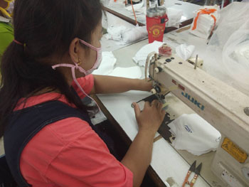 Female with long, dark hair pulled into low pony tail, wears mask and is stitching at sewing machine on a table with others.