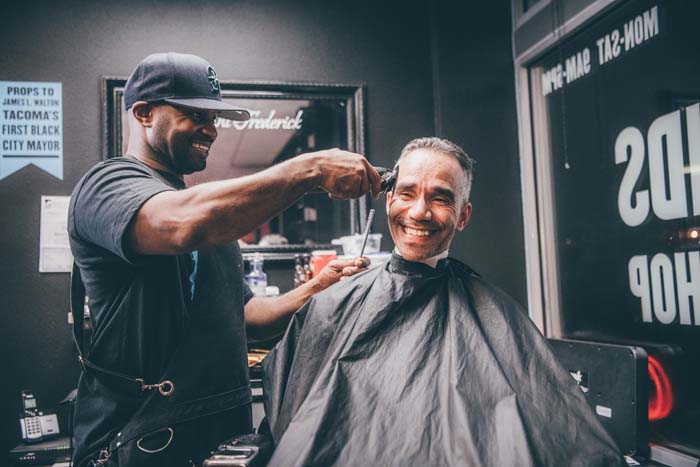 Adult male in Goodfellas Barbershop chair getting a cut