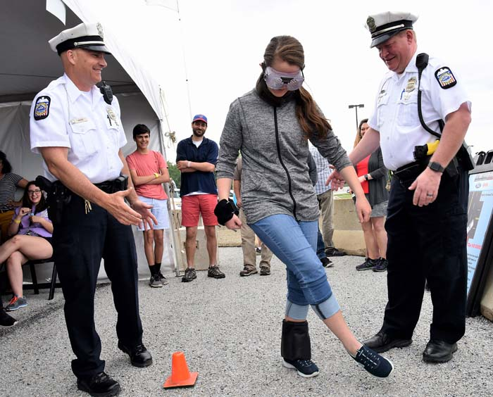 female student wears goggles while two police officers flank her stepping forward as students watch