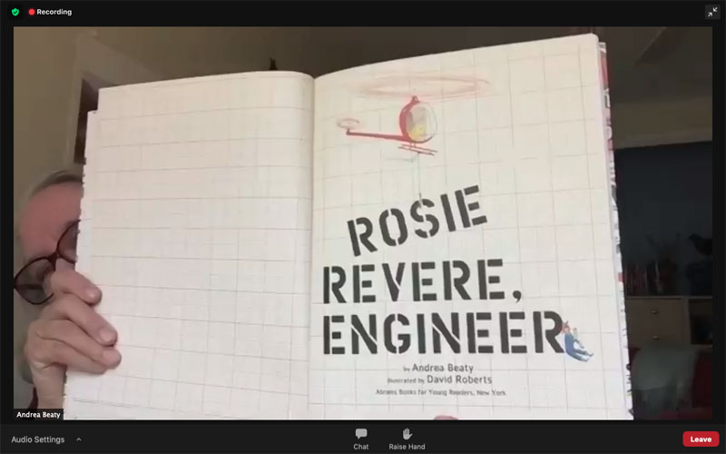 Eye glasses and right hand of author Andrea Beaty visible holding Rosie Revere, Engineer book in screen shot of online book reading