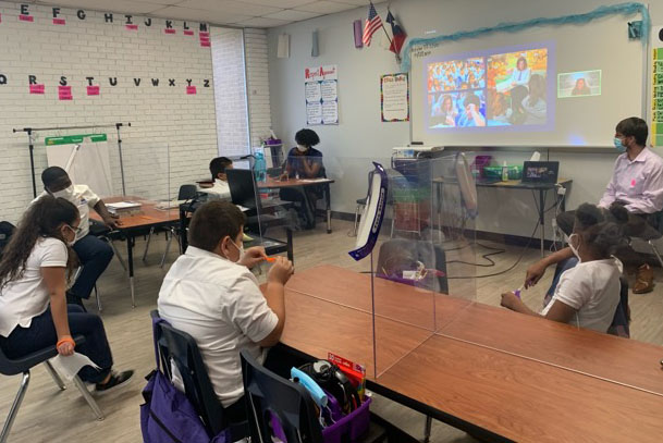 Children watching virtual book reading projected at front of Texas classroom