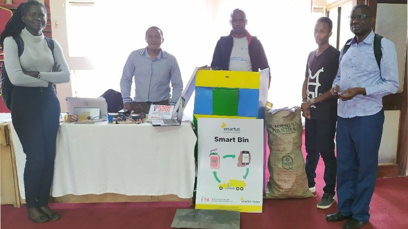 Group of students presenting their smart bin project inside a hall