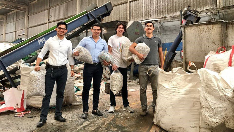 Four males holding bags of recycled materials
